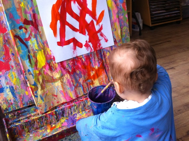 A 1-year old painting at an easel.